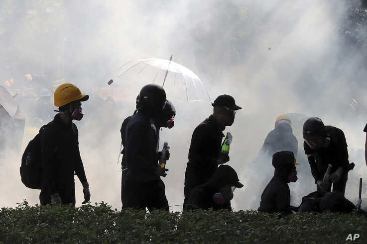 FILE - In this Sunday, Nov. 17, 2019, file photo, pro-democracy protestors react as police fire tear gas at Hong Kong…