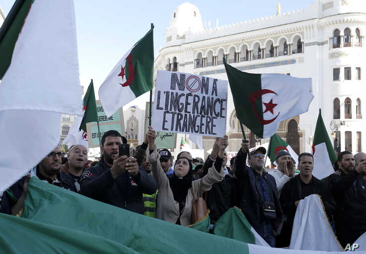 An Algerian woman holds a banner reading 'No to foreign interference' during a march against EU interference into Algeria's…