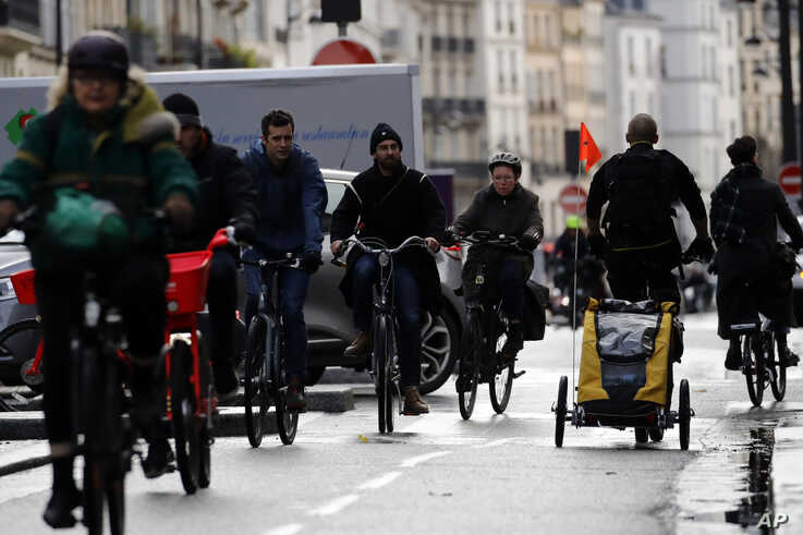 Parisians ride bicycles in the traffic jam, in Paris, Friday, Dec. 20, 2019. France's punishing transportation troubles may…