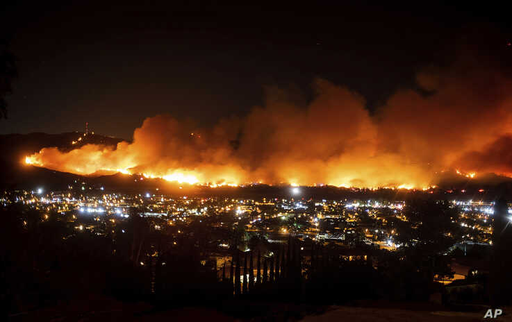 FILE - In this Oct. 31, 2019, file photo, smoke from a wildfire known as the Maria Fire billows above Santa Paula, Calif. A new…