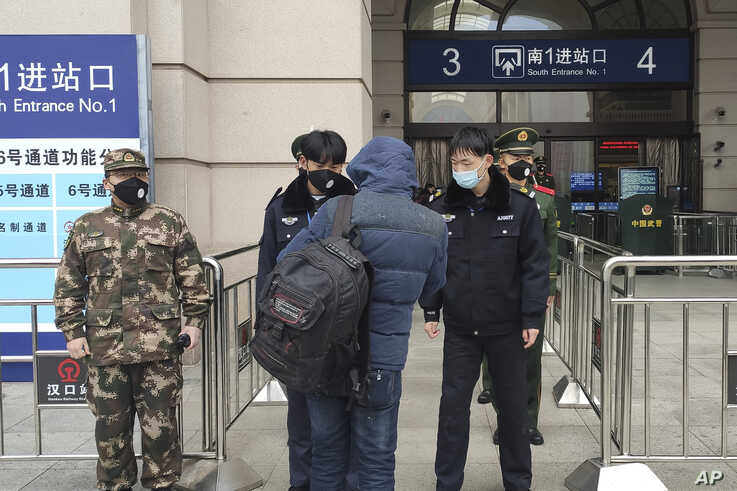 Security officers check a person at an entrance to the Hankou Railway Station in Wuhan in central China's Hubei Province,…