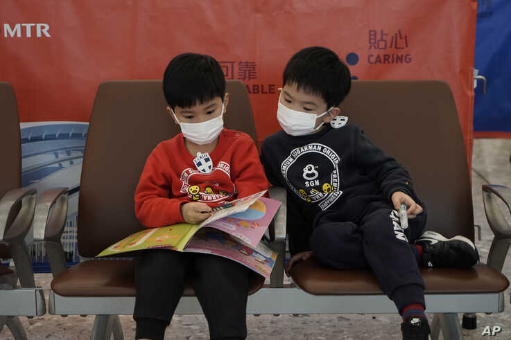 Passengers wear masks to prevent an outbreak of a new coronavirus in the high speed train station, in Hong Kong, Wednesday, Jan…