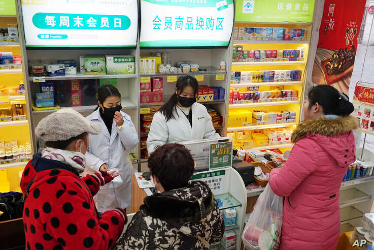 Staff sell masks at a Yifeng Pharmacy in Wuhan, Chin, Wednesday, Jan. 22, 2020. Pharmacies in Wuhan are restricting customers…