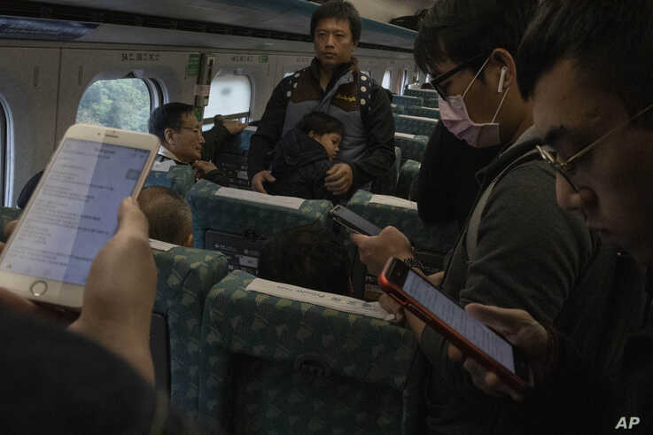 Travelers on a high speed train from Kaohsiung to Taipei read up on the post election news near central Taiwan's Taichung city…