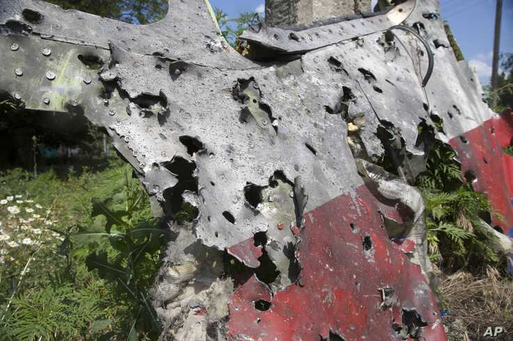FILE - In this Wednesday, July 23, 2014 file photo, a piece of the crashed Malaysia Airlines Flight 17 lies in the village of…
