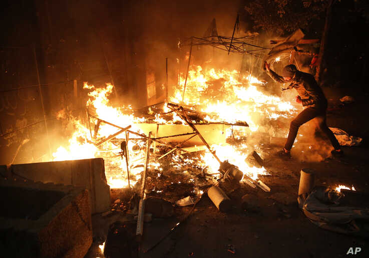 An anti-government protester tries to extinguishes a tent which set on fire by civilian men believed to be the private unit of…
