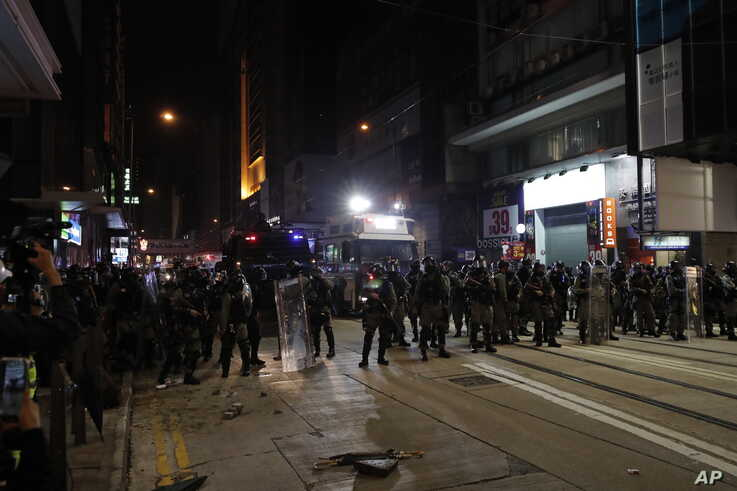 Police arrive to chase away protestors in Hong Kong, Wednesday, Jan. 1, 2020. Hong Kong toned down its New Year's celebrations…