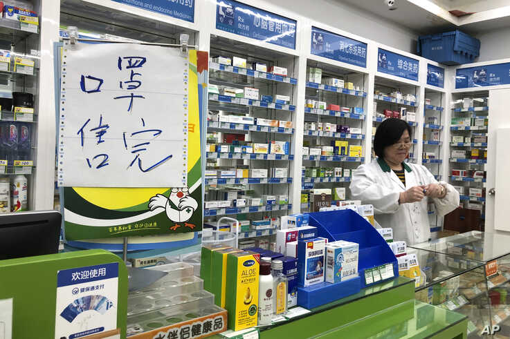 "Pharmacist Liu Zhuzhen stands near a sign reading ""face masks are sold out"" at her pharmacy in Shanghai, Tuesday, Jan. 21, 2020…"