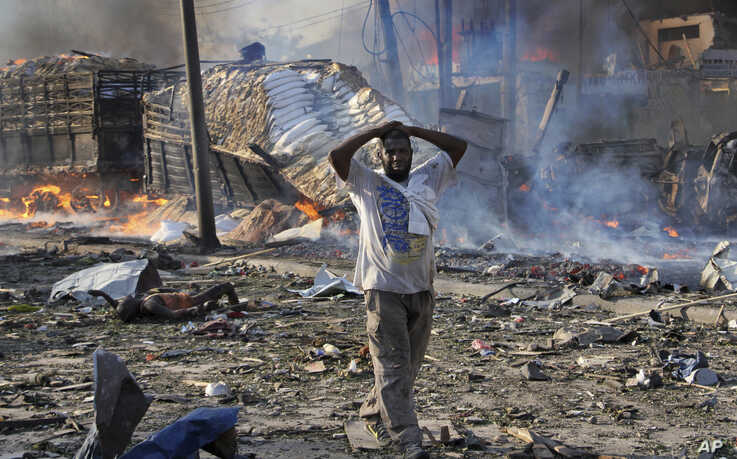 FILE -bIn this Saturday, Oct 14, 2017, file photo, a man walks past a dead body and destroyed buildings at the scene of a blast…