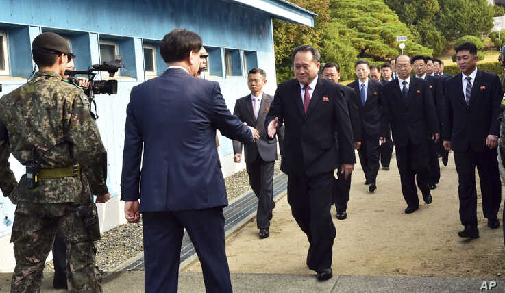 The head of the North Korean delegation Ri Son Gwon, center, is greeted by an unidentified South Korean official as Ri crosses…