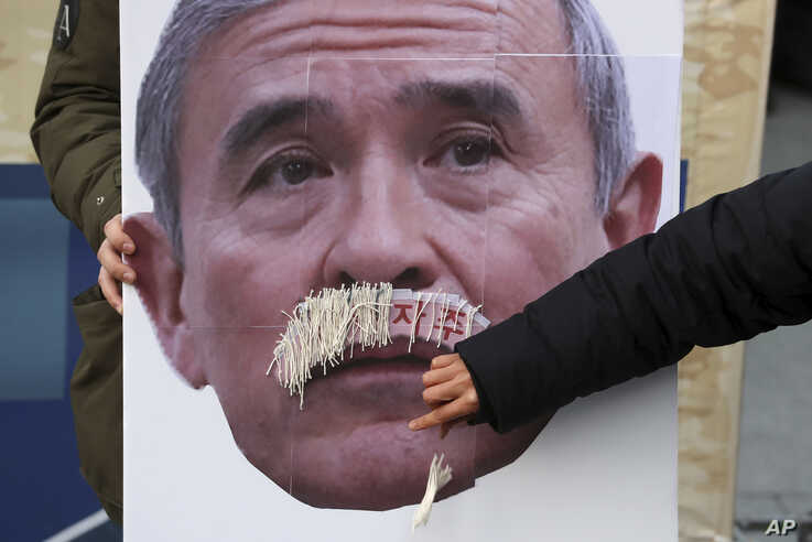 In this Dec. 13, 2019, photo, a protester plucks face mustache from a picture of U.S. Ambassador to South Korea Harry Harris…