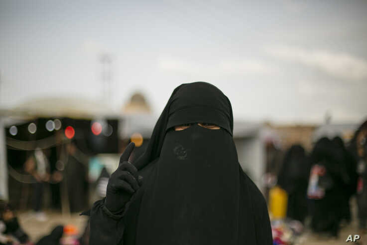 In this March 31, 2019 photo, a woman poses for a portrait at Al-Hol camp, which holds families of Islamic State members, near…