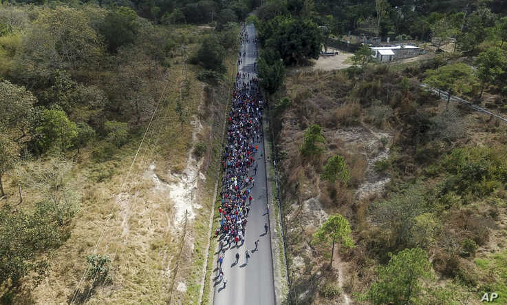 Migrants walk along a highway in hopes of reaching the distant United States, near Agua Caliente, Guatemala, Thursday, Jan. 16,…