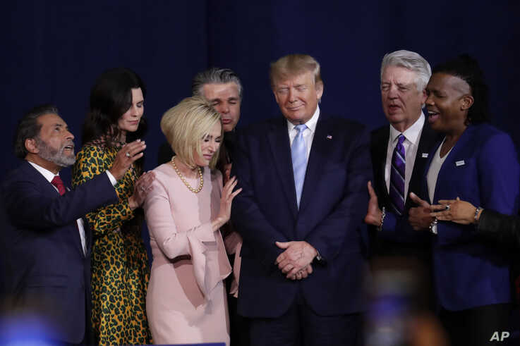 Faith leaders pray with President Donald Trump during a rally for evangelical supporters at the King Jesus International…