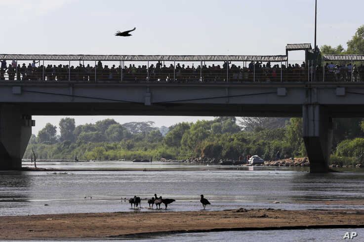 Migrants crowd the the bridge spanning the Suchiate River on the border between Guatemala and Mexico in Ciudad Hidalgo,…
