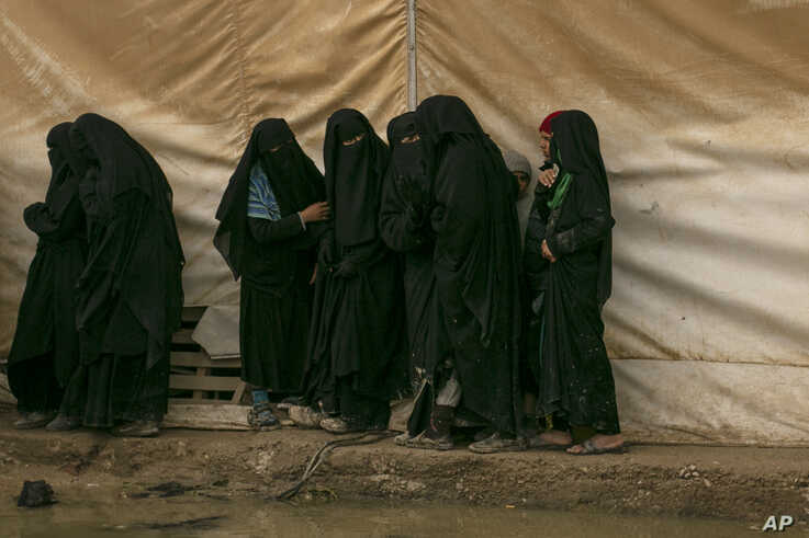 In this March 31, 2019 photo, women line up for aid supplies at Al-Hol camp, home to Islamic State-affiliated families near…