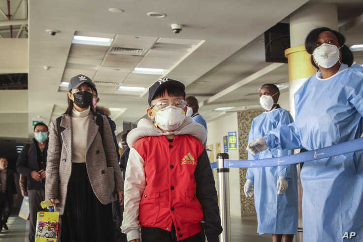Passengers arriving from a China Southern Airlines flight from Changsha in China are screened for the new type of coronavirus,…