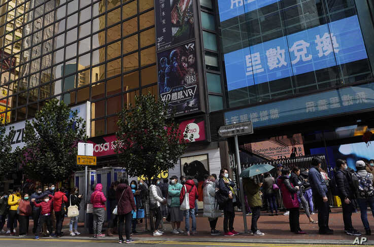 People queue up to purchase face masks outside a shop in Hong Kong, Monday, Jan. 27, 2020. Hong Kong announced it would bar…
