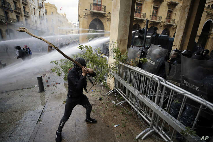 Anti-government demonstrators clash with riot police at a road leading to the parliament building in Beirut, Lebanon, Saturday,…