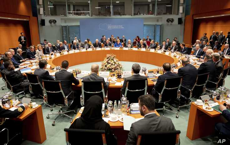 German Chancellor Angela Merkel, rear center, leads a conference on Libya at the chancellery in Berlin, Germany, Sunday, Jan…