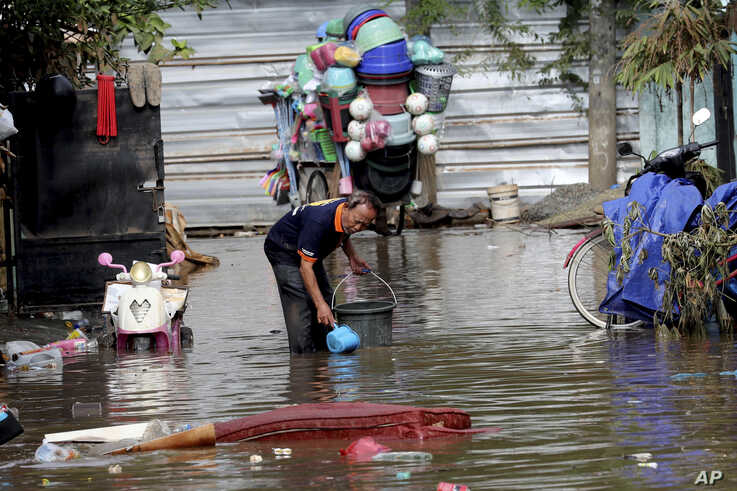 A man collects a water to clean his flooded house in Tanggerang on the outskirts of Jakarta, Indonesia, Friday, Jan. 3, 2020…