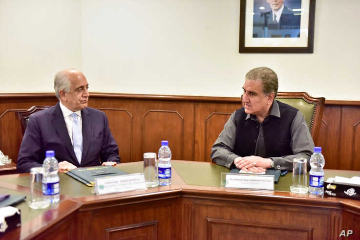 In this photo released by the Foreign Office, Pakistan's Foreign Minister Shah Mehmood Qureshi, right, meets U.S. envoy Zalmay…