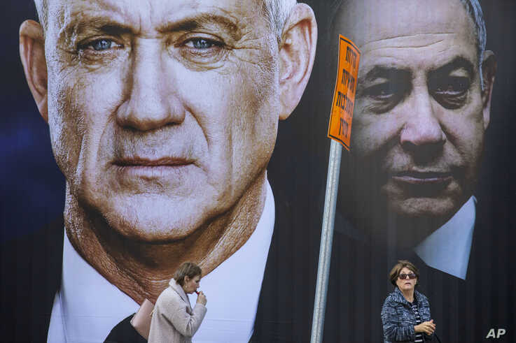 People walk by an election campaign billboard for the Blue and White party, the opposition party led by Benny Gantz, left, in…