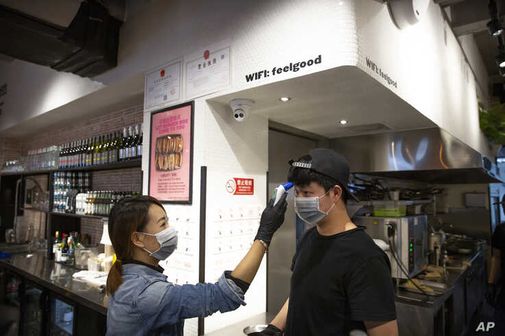 Manager Chen Tiantian measures an employee's temperature at a Moka Bros cafe in Beijing, Friday, Feb. 14, 2020. For Valentine's…