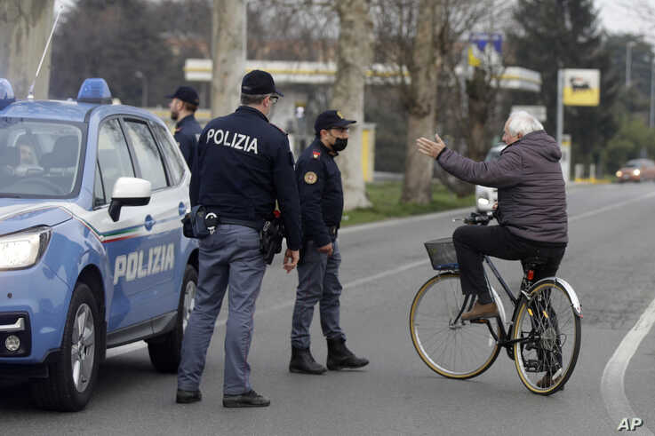 A cyclist talks to police officers controlling movements to and from the cordoned area in Casalpusterlengo, Northern Italy,…