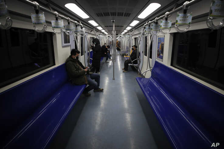 Commuters ride in a quiet subway train during the morning rush hour in Beijing, Monday, Feb. 17, 2020. Chinese authorities on…