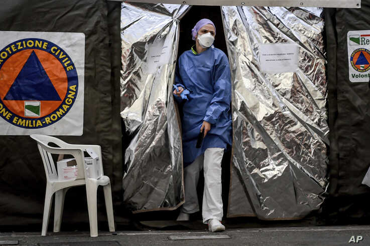 A paramedic wearing a mask gets out of a tent set up by the Italian Civil Protection outside the emergency ward of the Piacenza…