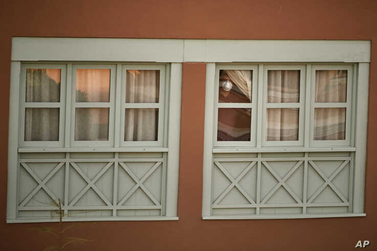 A man looks out of a window at the H10 Costa Adeje Palace hotel in La Caleta, in the Canary island of Tenerife, Spain,…
