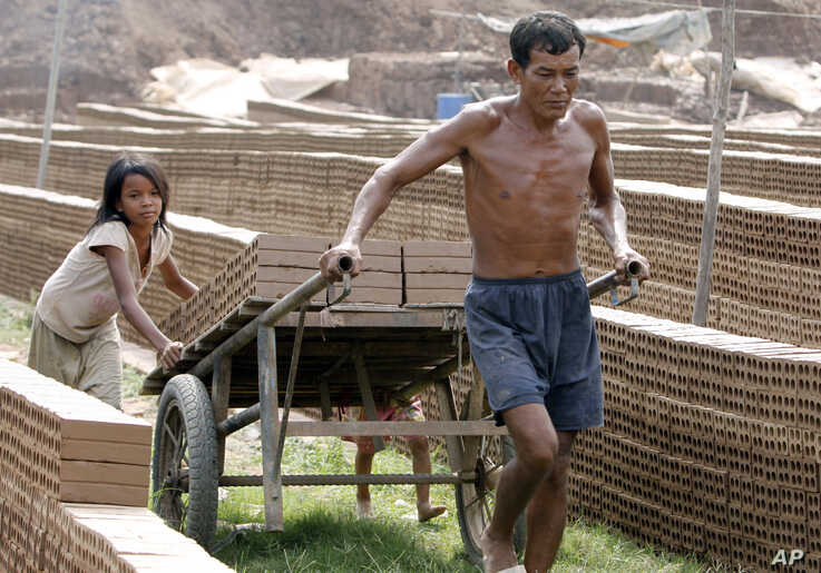 A Cambodian man pulls a cart loaded with bricks as helps to push by his daughter, behind, for preparing to dry under the sun…