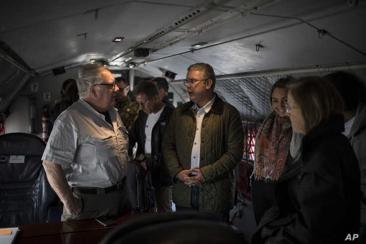 In this Jan. 29, 2020 photo, Howard Buffett, left, talks to Colombia's President Ivan Duque aboard an air force plane before…