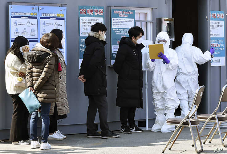 People suspected of being infected with the new coronavirus wait to receive tests at a medical center in Daegu, South Korea,…
