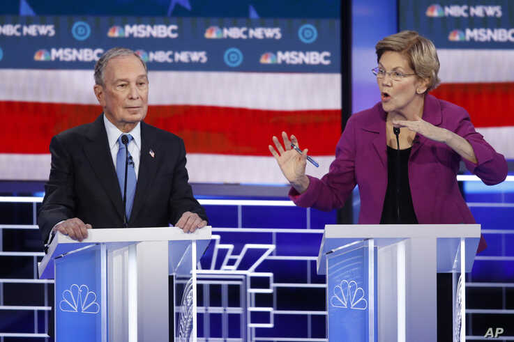 Democratic presidential candidates, former New York City Mayor Mike Bloomberg, left, listens as Sen. Elizabeth Warren, D-Mass.,…