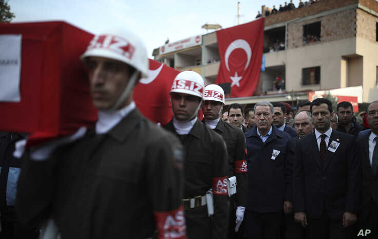 Turkey's Defence Minister Hulusi Akar, third right, attends a funeral ceremony for Halil Ibrahim Akkaya, one of Turkish…
