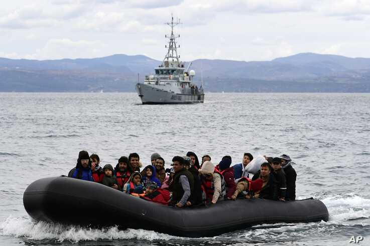 Migrants arrive with a dinghy accompanied by a Frontex vessel at the village of Skala Sikaminias, on the Greek island of Lesbos…