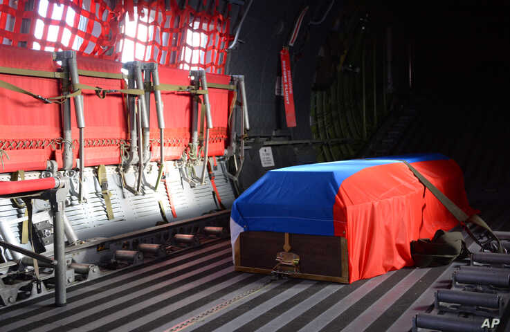 In this image provided by the Turkish Military, the Russian flag-covered coffin of Russian pilot Lt. Col. Oleg Peshkov has been…