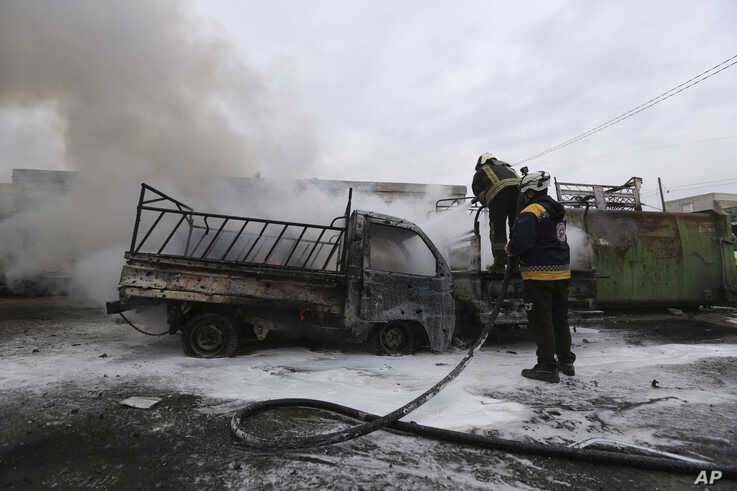 Firefighters hose a truck after a government airstrike in the city of Idlib, Syria, Tuesday, Feb. 11, 2020. The latest violence…