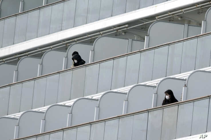 Masked passengers stand outside on the balcony of the cruise ship Diamond Princess anchored at Yokohama Port in Yokohama, near…