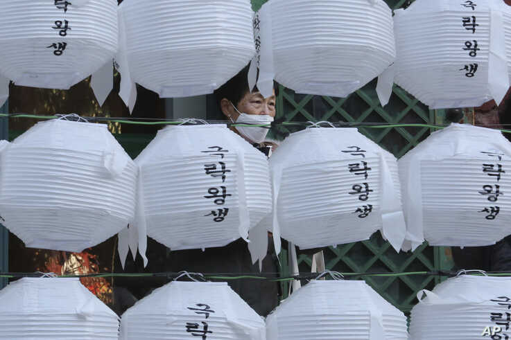 A woman wearing a face mask stands behind lanterns decorated for upcoming celebration of Buddha's birthday on April 30, at…