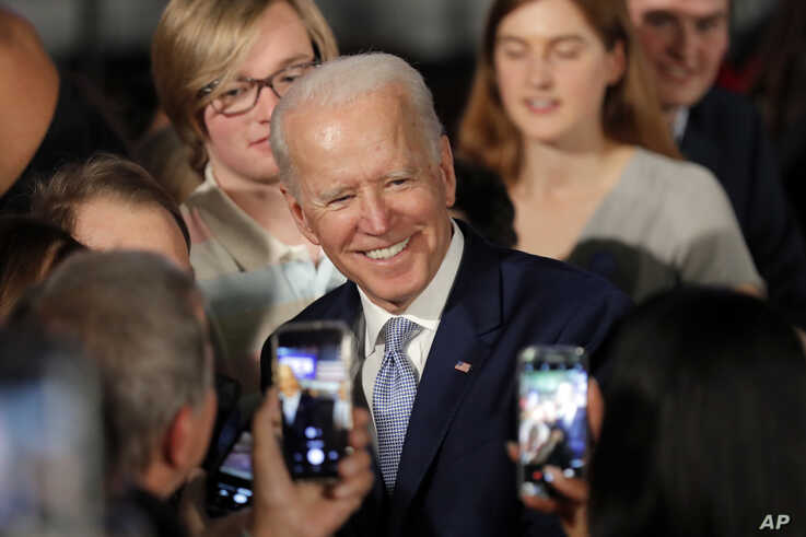 Democratic presidential candidate former Vice President Joe Biden poses for photos at a primary night election rally in…