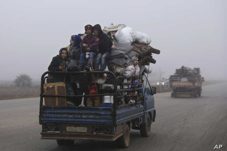FILE - This Dec. 23, 2019, file photo, civilians ride in a truck as they flee Maaret al-Numan, Syria, ahead of a government…