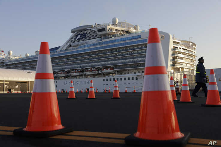 A security guard stands near the quarantined Diamond Princess cruise ship Thursday, Feb. 13, 2020, in Yokohama, near Tokyo…
