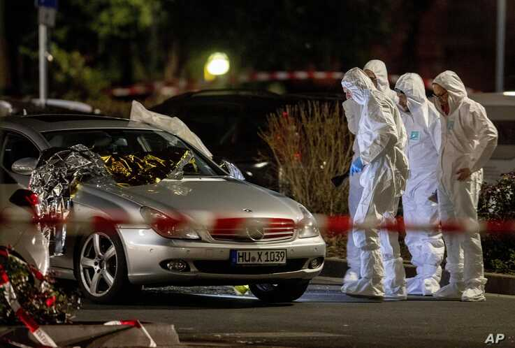 Forensics investigate at the scene after a shooting in central Hanau, Germany Thursday, Feb. 20, 2020. Eight people were killed…