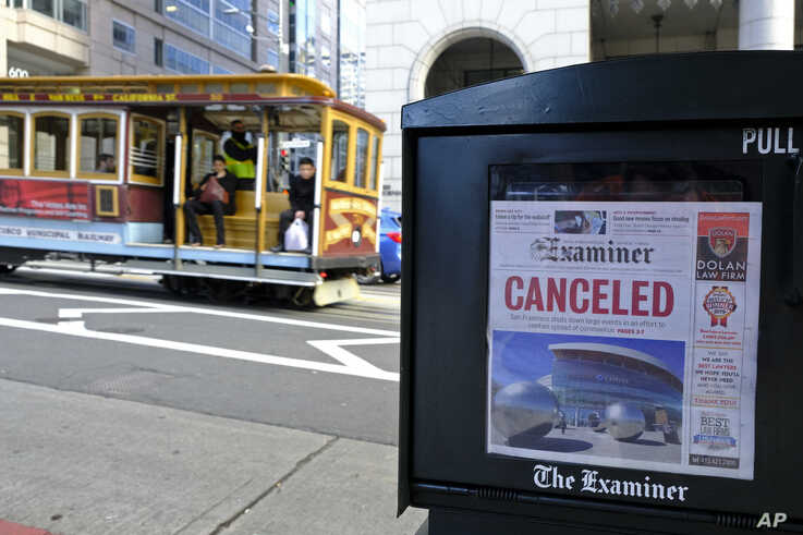 A newspaper headline announcing the closure of large events is displayed as a cable car goes down California Street, Friday,…