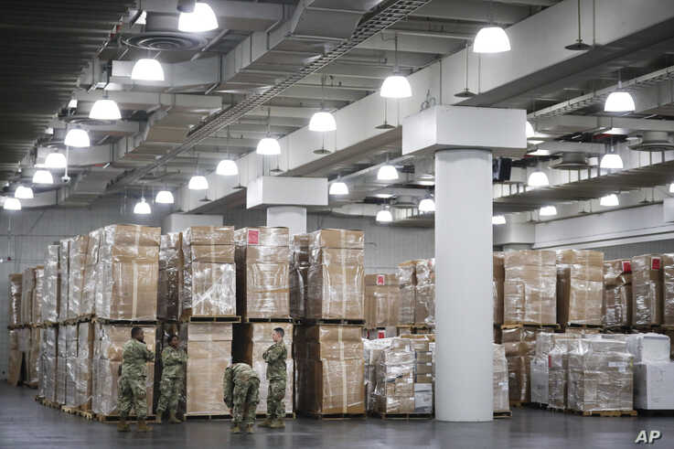 U.S. National Guard members stand beside crates of medical supplies at the Jacob Javits Center, Monday, March 23, 2020, in New…
