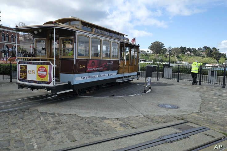 A cable car operator looks out toward the Golden Gate Bridge while standing at the near-empty Hyde Street turnaround Monday,…