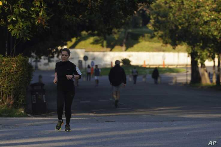 A woman runs in downtown Rome, Thursday, March 19, 2020. Italian officials are warning they might impose tougher restrictions…